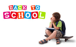 Kid with back to school theme isolated on white. Kid sitting on skateboard with back to school theme isolated on white Royalty Free Stock Photography