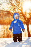 Kid on background of  winter landscape in sunset backlight. A ch Stock Photography