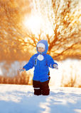 Kid on background of  winter landscape in sunset backlight. A ch Stock Photo