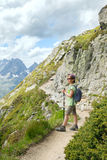 Kid with backpack is hiking by mountain trail Stock Images