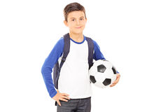 Kid with backpack holding a football Stock Photos
