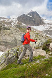 Kid with backpack and sticks in mountains Royalty Free Stock Images
