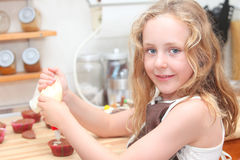 Kid baking or cooking. Child cooking,baking and helping decorate cupcakes Stock Photos