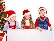 Kid with banner near Christmas tree. Royalty Free Stock Photos