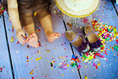 Kid barefooted legs in against the confetti and garlands - selective focus, copy space royalty free stock images