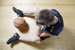 Kid with basketball on floor royalty free stock photo