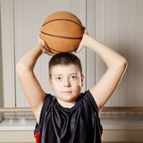 Kid with basketball over head Stock Image