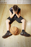 Kid with basketball sitting on floor Stock Photography