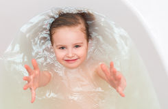 Kid in a bathtub, reaching out, topshot Stock Photography