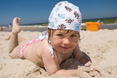 Kid on the beach. Little girllying on sand on beach Stock Photography