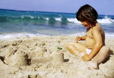 Kid on the beach. A kid build a castel with sand on a beach Stock Image