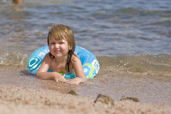 Kid on the beach. Kid lying on the beach in warm sea transparent water looking at you with smile Royalty Free Stock Images