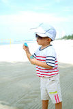 Kid On Beach Blowing Bubbles Stock Photography