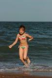 Kid on the beach, Crimea. Little girl enjoy sunshine, sea and summertime Stock Image