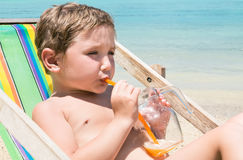 Kid on the beach drinking juice from glass mug with a straw Royalty Free Stock Photos