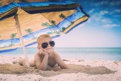 Kid on a beach. Instagram stylization. Little kid in a sunglass lying on a sandy beach under colorful umbrella, Instagram stylization royalty free stock photos