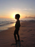Kid on the beach in silhouette. Kid in the beach on the sunset Stock Photos