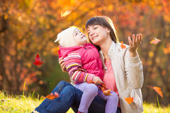 Kid and beautiful mother playing outdoor in autumn park Stock Image