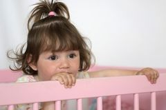 Kid in Bed. Little girl standing in her pink bed royalty free stock photos
