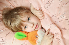 Kid in bed with toy Stock Photography