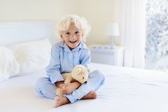 Kid in bed. Winter window. Child at home by snow. Royalty Free Stock Photo