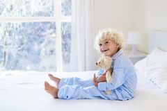 Kid in bed. Winter window. Child at home by snow. Stock Image