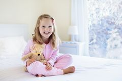 Kid in bed. Winter window. Child at home by snow. Stock Photos