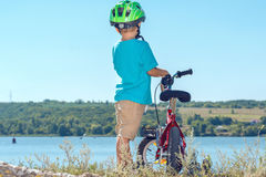 Kid with a bicycle near the river stock photo
