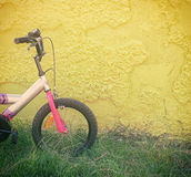 Kid bicycle next to yellow textured wall Royalty Free Stock Photography