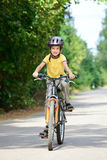Kid on a bike. Young boy riding bicycle on a summer day Royalty Free Stock Photo