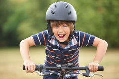 Kid with bike and helmet. Smiles while having fun stock image