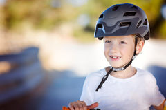 Kid biking in helmet Stock Images