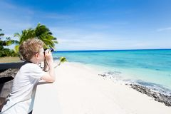 Kid with binoculars. Wide angle view of little curious boy with binoculars looking at gorgeous turquoise lagoon at beautiful fiji island, vacation concept, copy Royalty Free Stock Image