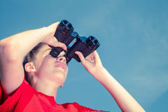 Kid birdwatching  outdoor. Low angle view of birdwatcher teen boy wearing red tshirt looking through binoculars at birds against blue summer sky Stock Images