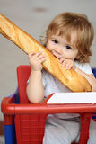 Kid biting French bread in shopping trolley Stock Image