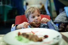 Kid biting kebab. In an asian restaurant stock images