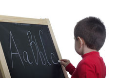 Kid at blackboard. Isolated over white background Stock Photos