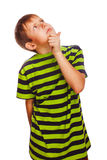 Kid blond boy in green T-shirt thinks scratching Royalty Free Stock Photo