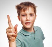Kid blond boy shaggy raised thumbs up is good idea Stock Photo