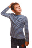 Kid blond boy in striped sweater thinks scratching Stock Photo