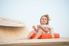 Kid with blond hair have fun outdoor. Child sit in ring buoy on sunny day. Little boy with lifebuoy on tropical beach. Summer vaca. Tion and leisure. Safety Stock Photo