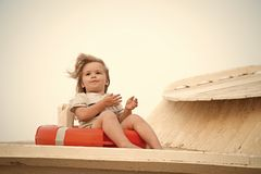 Kid with blond hair have fun outdoor. Child sit in ring buoy on sunny day. Little boy with lifebuoy on tropical beach stock photo