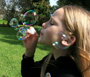 Kid Blowing Bubbles. A cute white caucasian girl child sitting in the garden blowing bubbles Royalty Free Stock Photos
