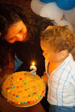 Kid blowing candles on birthday cake.