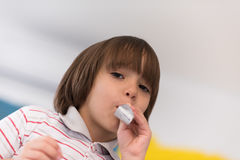 Kid blowing a noisemaker Stock Images