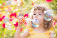 Kid blowing soap bubbles. Happy kid blowing soap bubbles outdoors in spring park royalty free stock photo