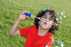 Kid Blowing Soap Bubbles in Summer stock photo