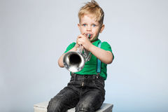 Kid Blowing Trumpet. Isolated Young Boy Blowing Trumpet Royalty Free Stock Image