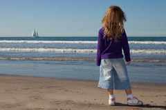 A kid and a boat. A little girl standing by the the ocean and looking at the sail boat Stock Photo