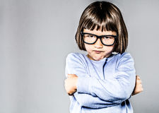 Kid body language with sulking, pouting small child crossing arms. Kid body language with sulking, pouting small child crossing her arms expressing attitude Stock Image